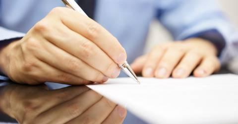 man ondertekent een document